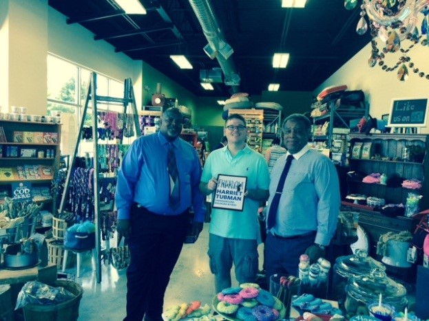 SBA Del. Deputy Director John Banks (left) and 'Tubman Byway' Chair Ron Rucker (right) present Yarn & Bone owner Matt Moorefield with 'Tubman Byway storefront seal to visibly mark his business as 'Tubman Byway affiliated.'